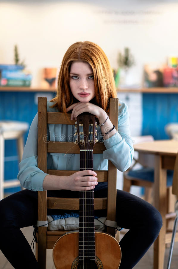 Девушка сидя с акустической гитарой стоковая фотография