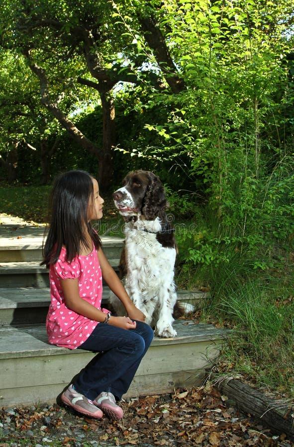 Девушка сидя с ее собакой стоковое изображение