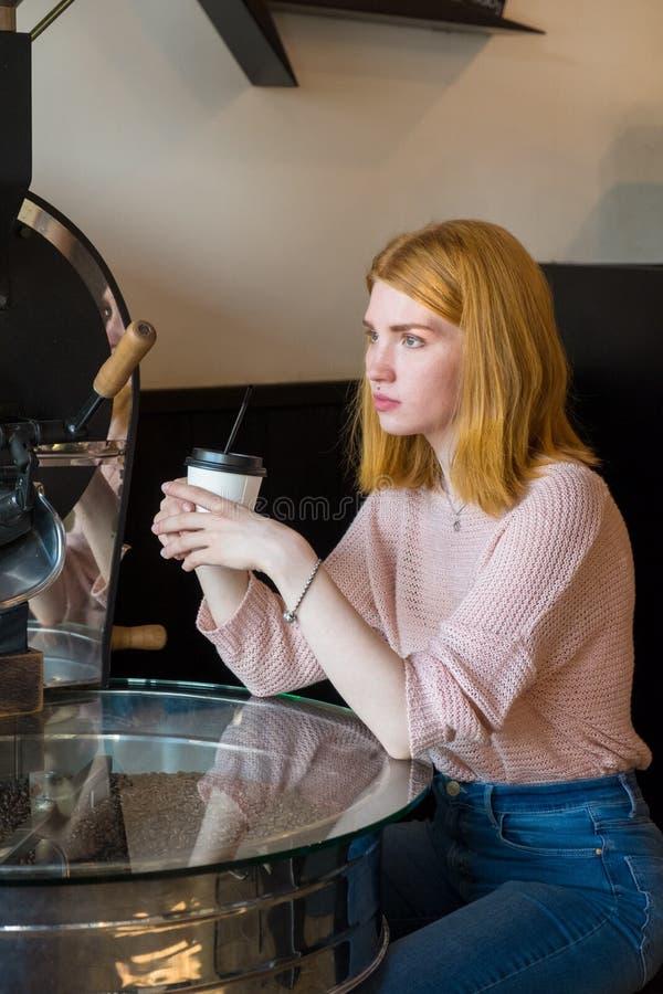Девушка сидя с чашкой кофе стоковое изображение
