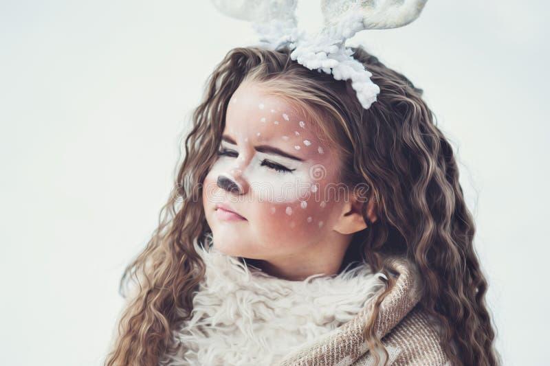 Девушка сказки Портрет маленькая девочка в олене одевает с покрашенной стороной в лесе зимы стоковое изображение