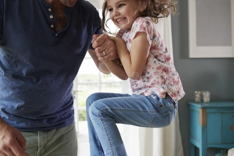 Девушка скача вверх и держа руку ½ s ¿ dadï дома, средний раздел стоковое фото