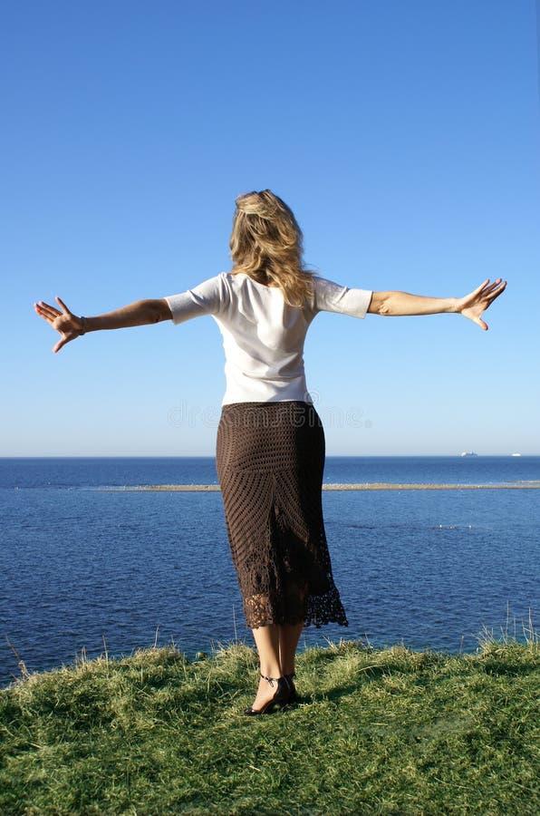 Девушка скача внутри к морю стоковые фото