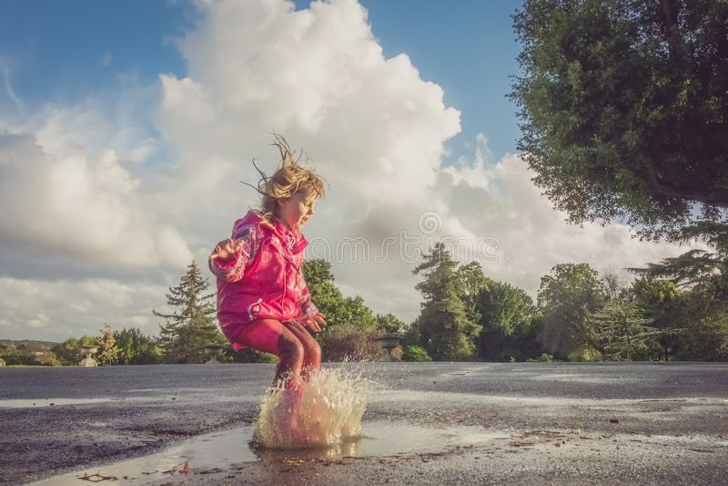 Девушка скача в большую лужицу стоковые изображения