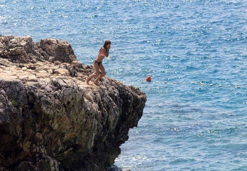 Девушка скача в воду от скалы стоковое фото