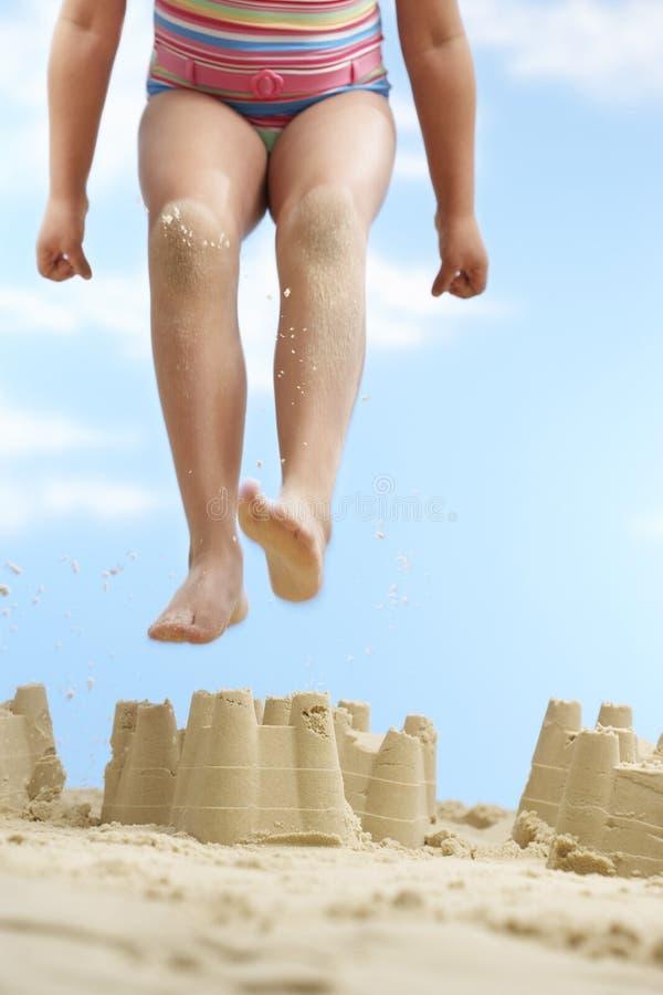 Девушка скача на замок песка стоковое изображение