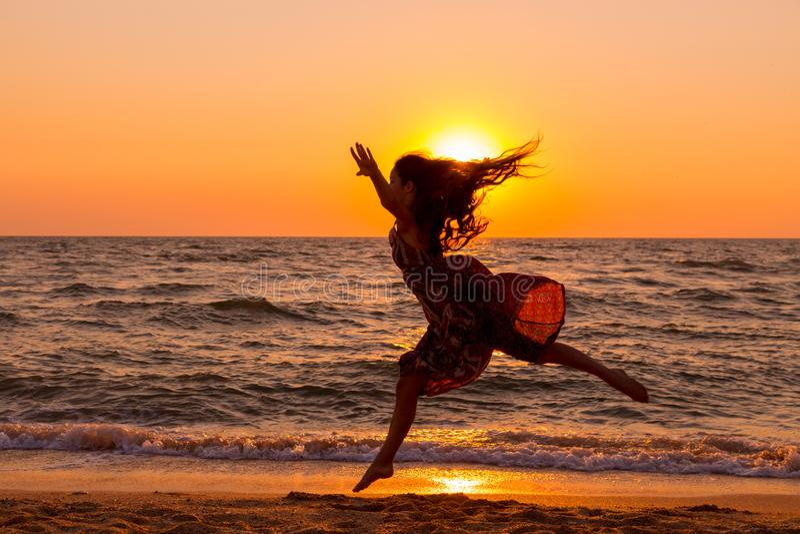 Девушка скача на морское побережье на восходе солнца стоковое изображение rf