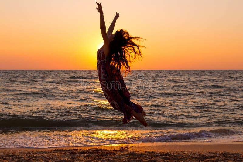 Девушка скача на морское побережье на восходе солнца стоковое изображение
