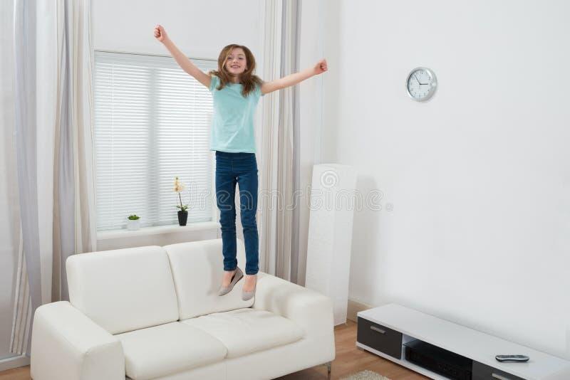 Девушка скача на софу стоковая фотография