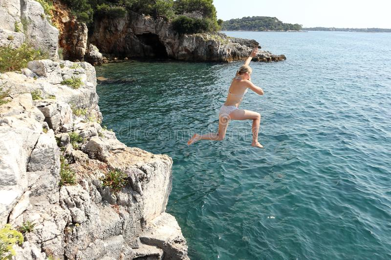 Девушка скачет в воду стоковая фотография