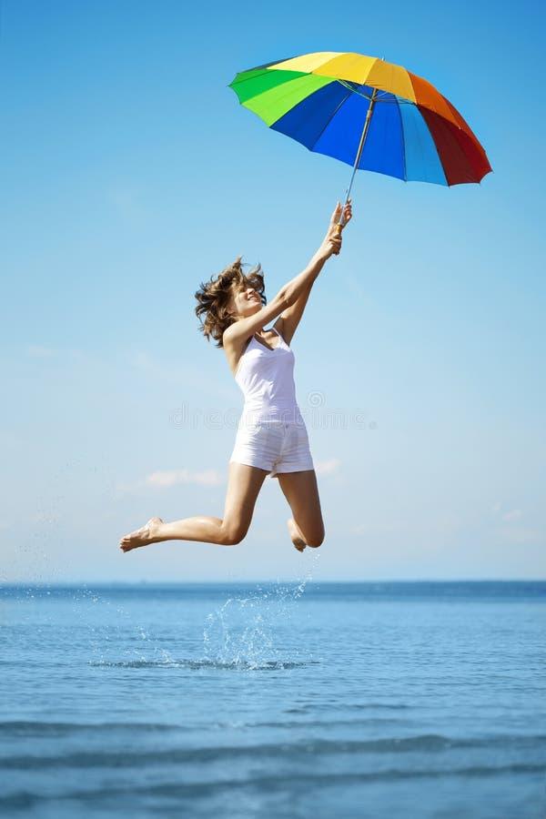 девушка скачет зонтик радуги стоковое изображение rf