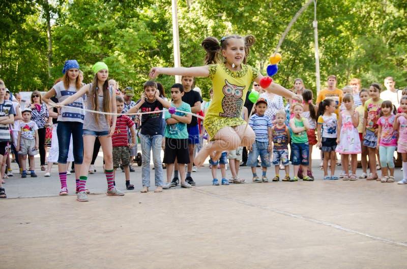 Девушка скачет над веревочкой, который держат девушки в костюмах пирата на партии пирата стоковые изображения