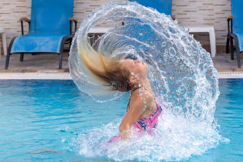 Девушка слегка ударяя волосы в бассейне в солнце стоковые фотографии rf