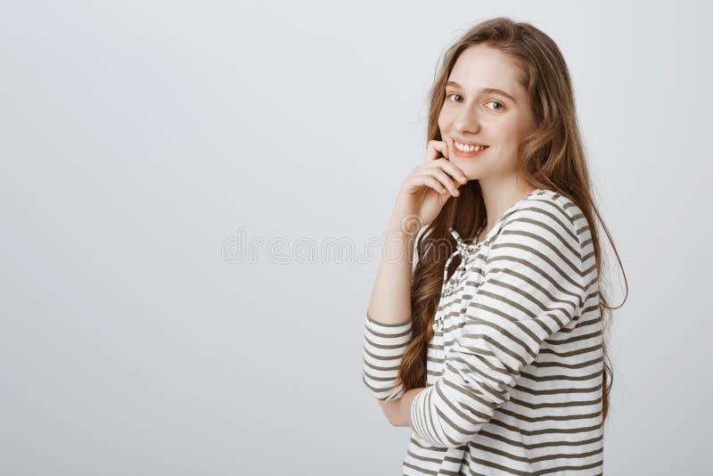 Девушка слушает к вашему рассказу при женщина интереса счастливая привлекательная кавказская стоя в профиле над серой предпосылко стоковые изображения