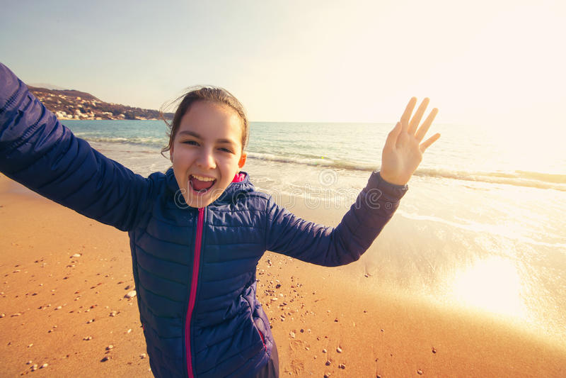 Девушка смеется над на пляже в солнечном зимнем дне стоковая фотография