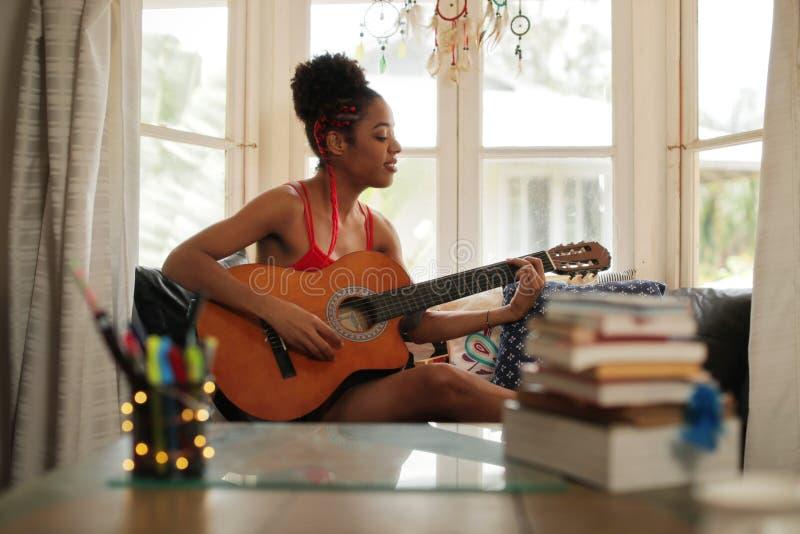 Девушка смешанной гонки поя и играя классическую гитару дома стоковое фото rf
