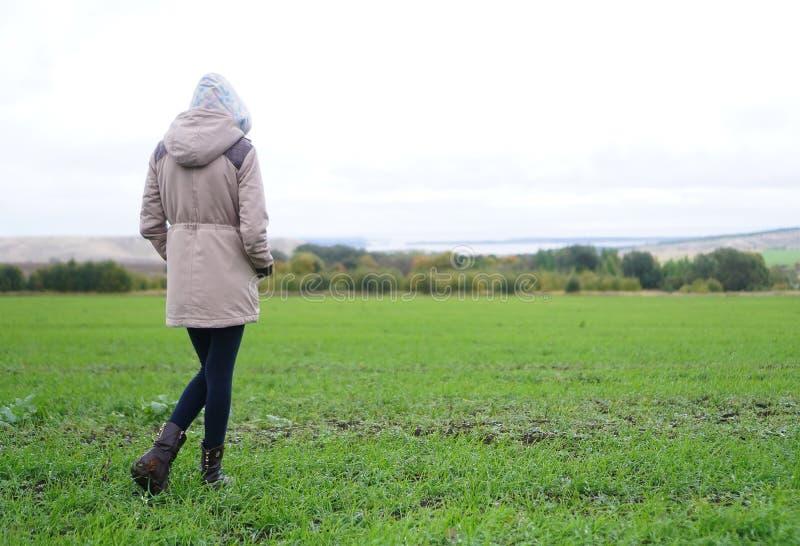 Девушка смотрит в осень в луге th стоковая фотография