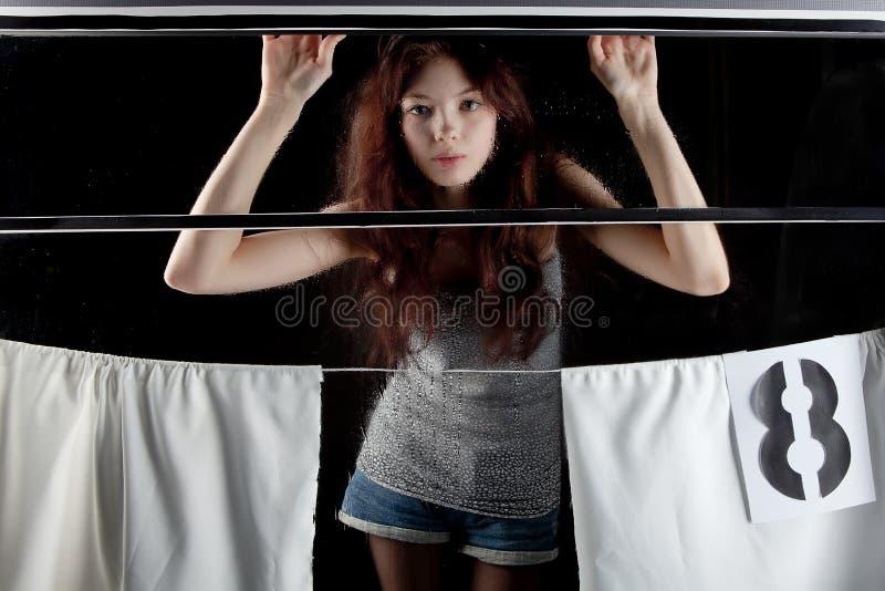 Девушка смотрит из окна поезда стоковая фотография rf
