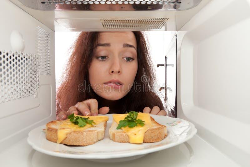 девушка смотрит микроволну стоковое фото rf