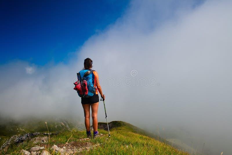 Девушка смотрит afar в тумане на долине горы во время прогулки стоковая фотография rf