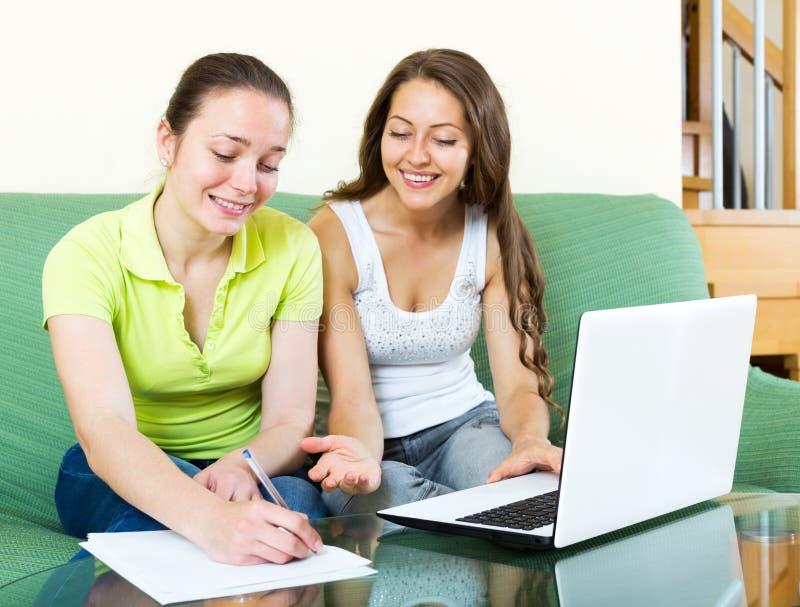 Девушка смотря бумаги с компьтер-книжкой стоковые изображения rf