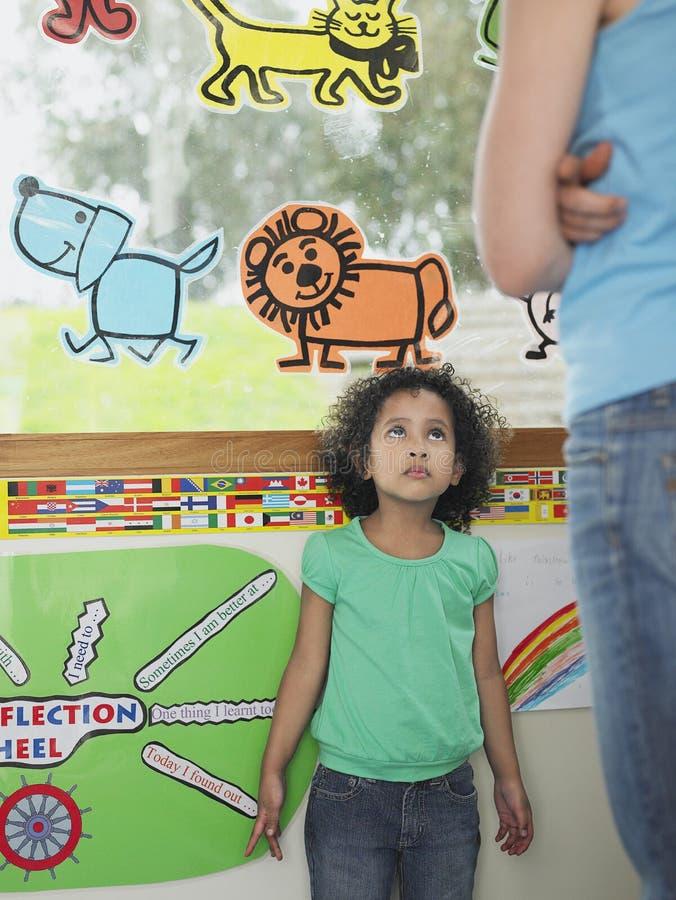 Девушка смотря вверх на учителе в классе стоковое фото rf