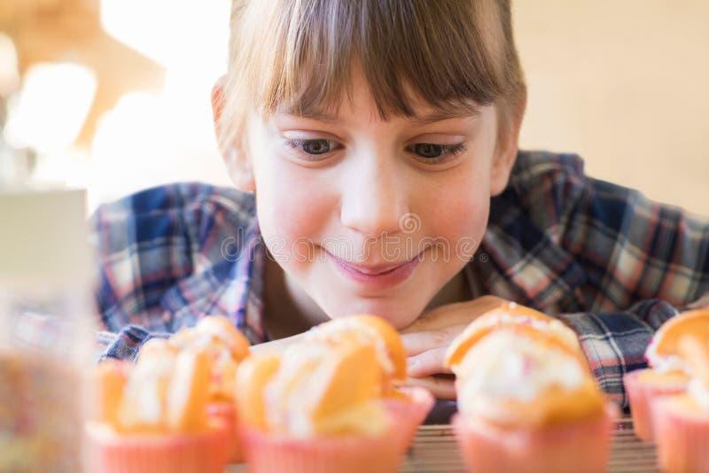 Девушка смотря голодно дома сделанные торты чашки стоковые изображения rf