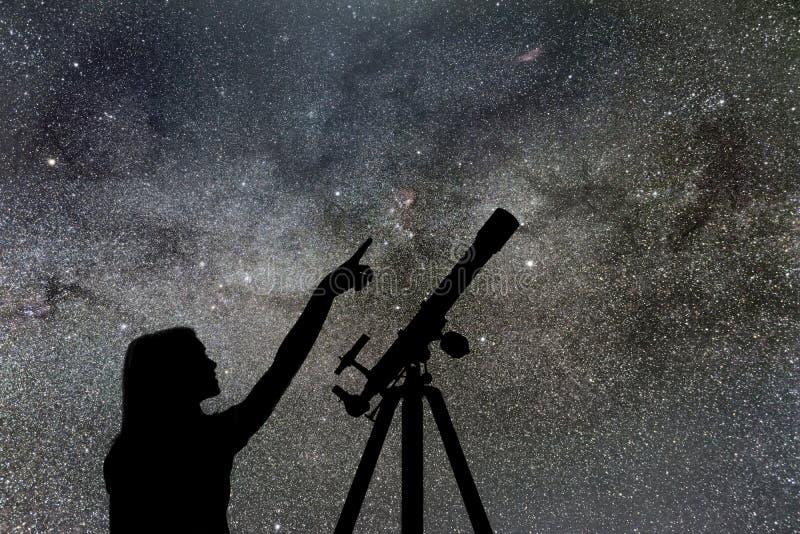Девушка смотря звезды Млечный путь телескопа стоковое фото