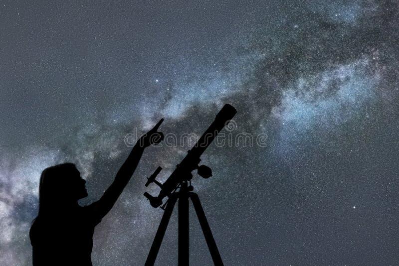 Девушка смотря звезды Млечный путь телескопа стоковая фотография rf