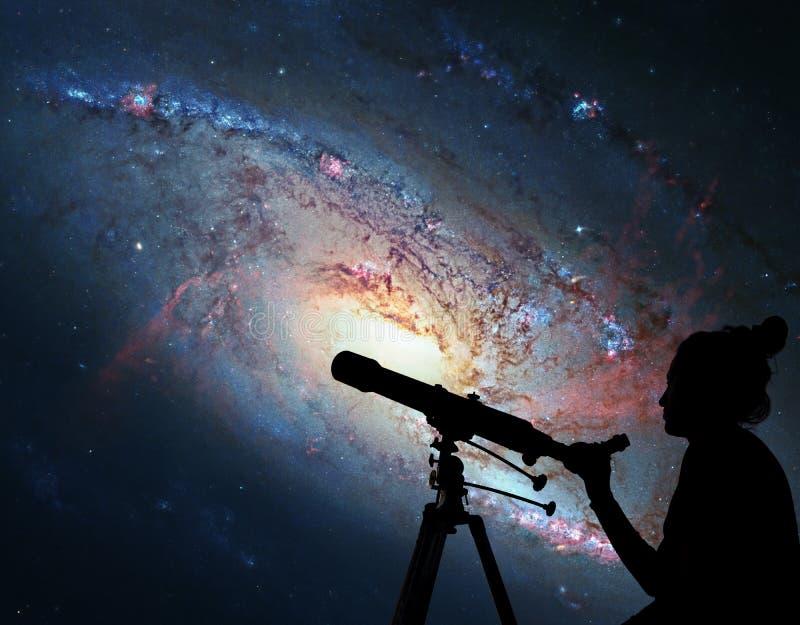 Девушка смотря звезды с телескопом Спиральная галактика M106 стоковая фотография