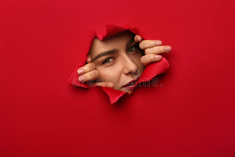 Девушка смотря из отверстия в бумаге стоковые фото