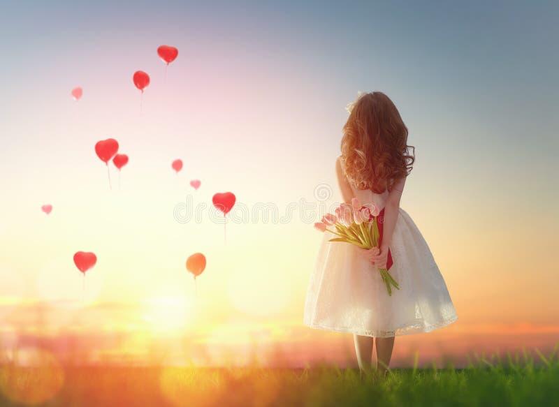 Девушка смотря красные воздушные шары стоковая фотография rf