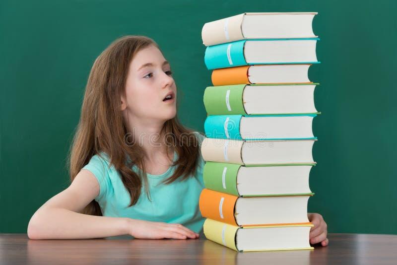Девушка смотря стог книг стоковое фото rf