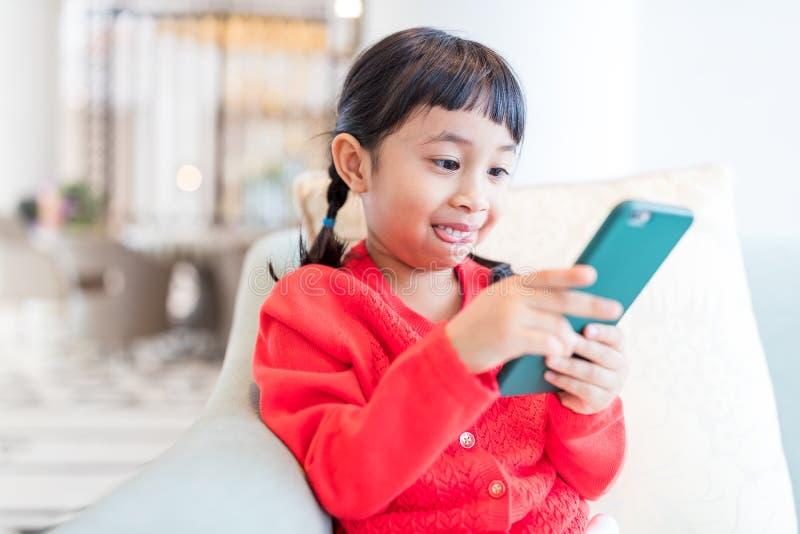 Девушка смотря умный телефон стоковая фотография rf