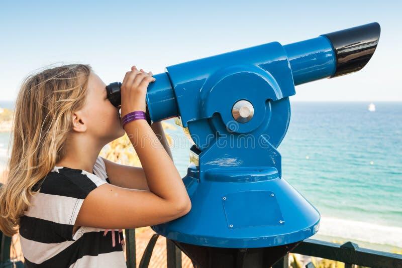 Девушка смотря через неподвижный оплаченный телескоп стоковая фотография