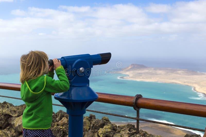 Девушка смотря через телескоп на острове и море, Лансароте стоковые изображения rf