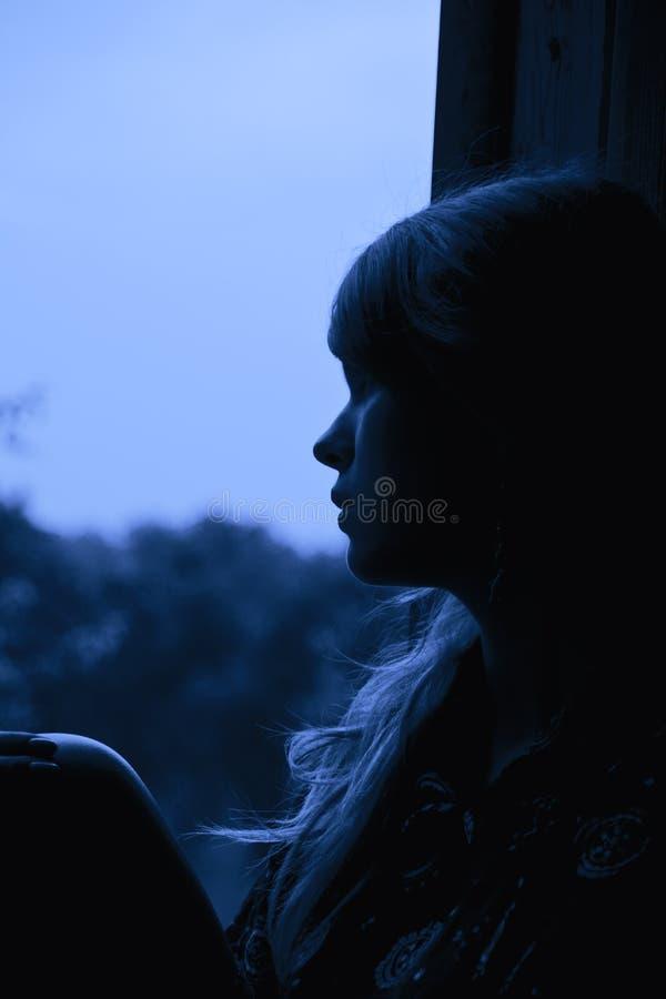 девушка смотря outdoors сидя окно стоковые фото