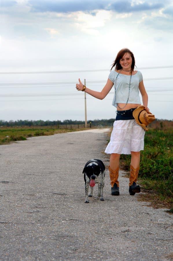 девушка собаки ее hitchhiking стоковые фотографии rf