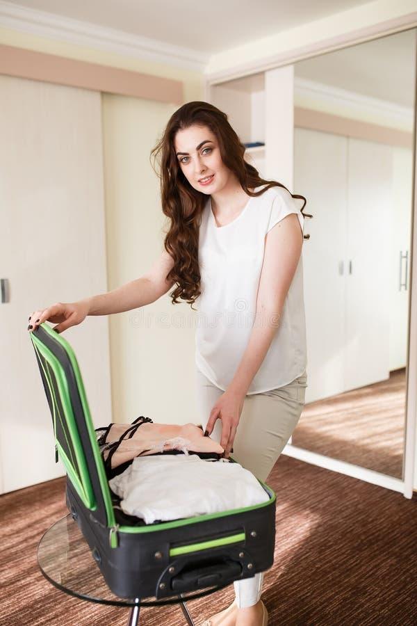 Девушка собирает чемодан в гостиничном номере стоковая фотография rf