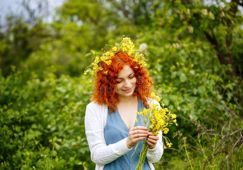 Девушка соткет венок wildflowers стоковое изображение rf
