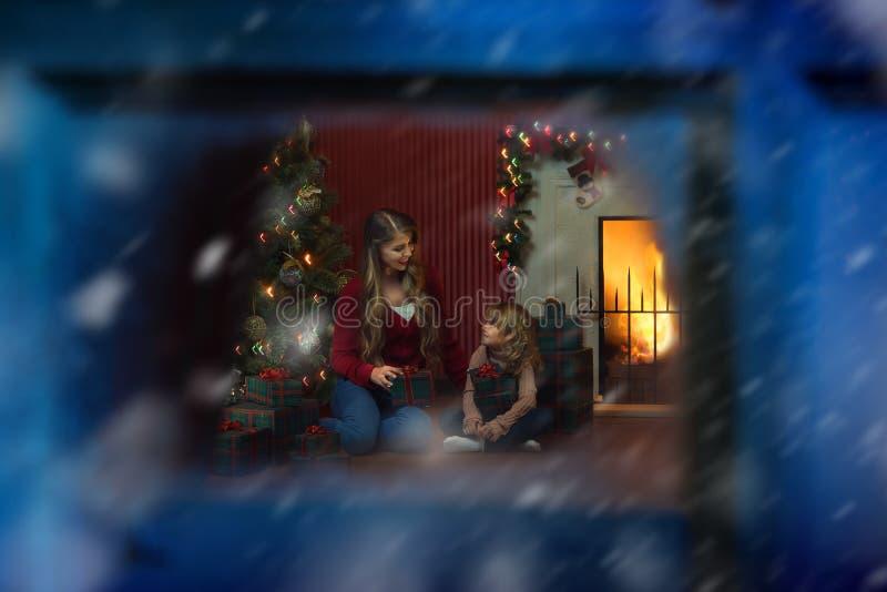 Девушка со своей мамочкой в окружении Рождества стоковые изображения rf