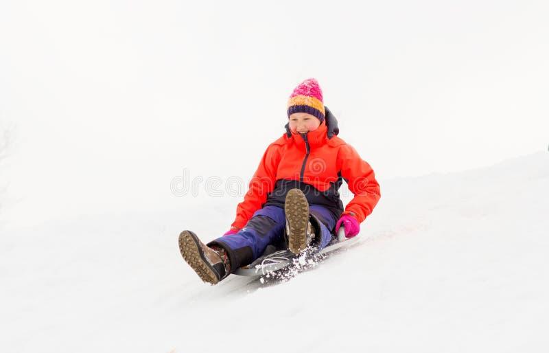 Девушка сползая вниз на скелетон поддонника снега в зиме стоковые фото