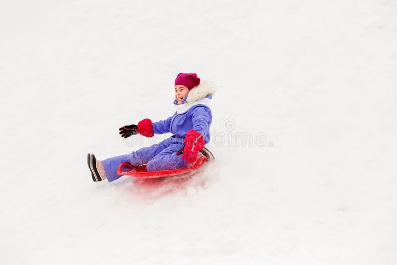Девушка сползая вниз на скелетон поддонника снега в зиме стоковое фото rf
