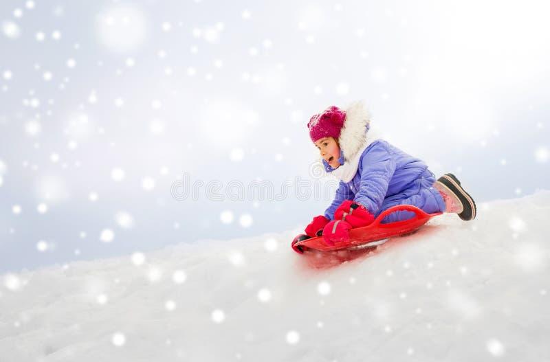 Девушка сползая вниз на скелетон поддонника снега в зиме стоковые изображения rf