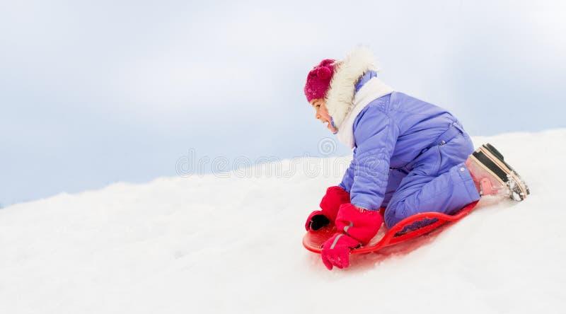 Девушка сползая вниз на скелетон поддонника снега в зиме стоковые изображения