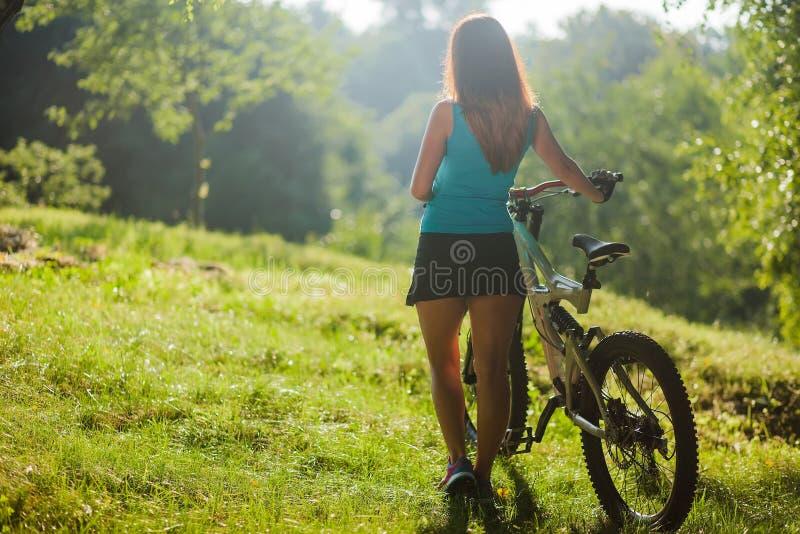 Девушка спорта на таблетке владением велосипеда цифровой стоковое изображение rf