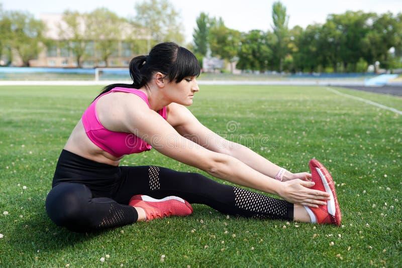 Девушка спорта фитнеса в sportswear моды делая тренировку в улице, на открытом воздухе спорт фитнеса йоги стоковое изображение rf