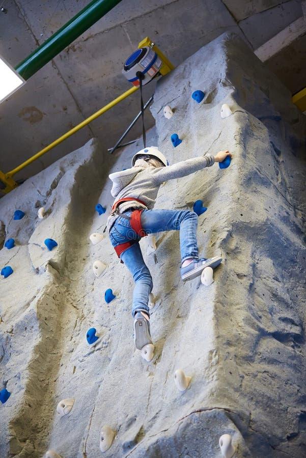 Девушка спортсмена взбирается в парке спорта на стене стоковая фотография