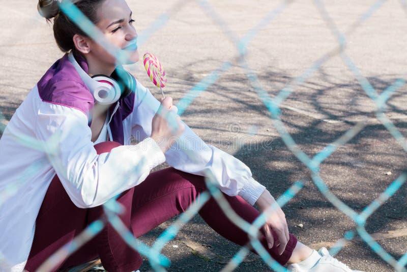 Девушка спорт есть конфету Outdoors стоковая фотография rf