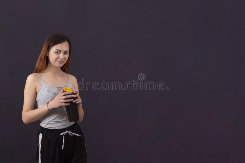 Девушка спорт после игры напитков спорт от шейкера с влажной рубашкой от copyspace пота стоковое изображение rf