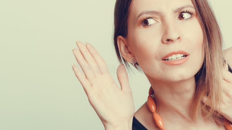 Девушка сплетни подслушивая с рукой к уху стоковое фото rf
